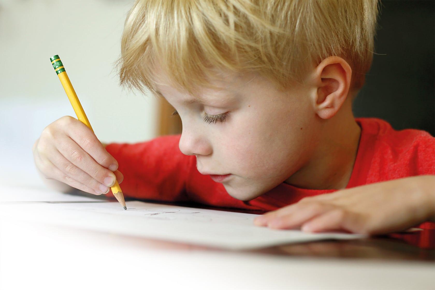La scolarité - Enfant qui apprend à écrire - École Expérimentale de Bonneuil